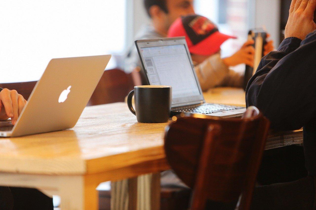 カフェでノートパソコンを開く男性
